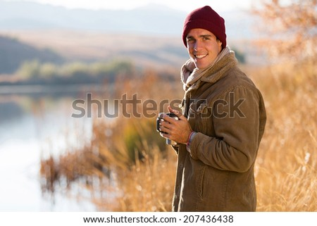 portrait of happy man drinking coffee outdoors in fall by the lake - stock photo