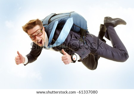 Portrait of happy man flying with parachute and showing thumbs up