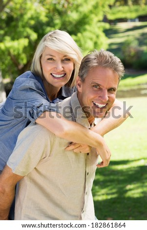 Portrait of happy man giving piggyback ride to woman in park