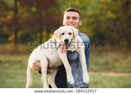 Portrait of happy man holding dog Labrador in hands in park