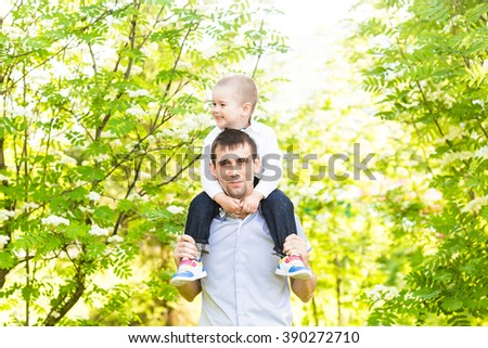 Portrait of happy man holding his son on neck outdoors - stock photo