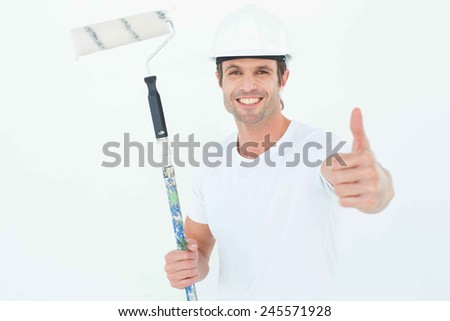 Portrait of happy man holding paint roller while gesturing thumbs up on white background