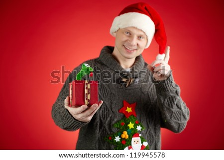 Portrait of happy man in Santa cap holding toy snake in open giftbox - stock photo