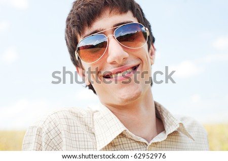 portrait of happy man in sunglasses against blue sky