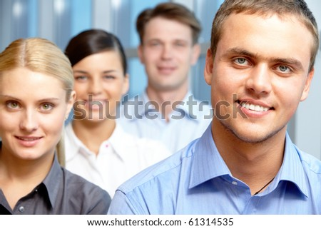 Portrait of happy man looking at camera with partners on background