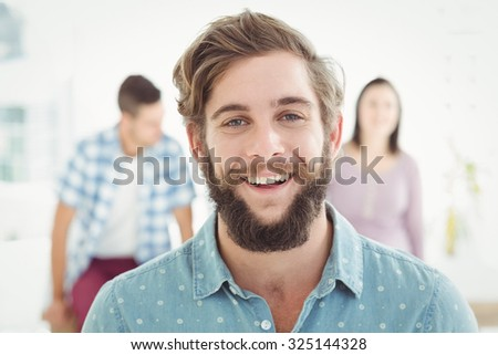 Portrait of happy man standing at office - stock photo