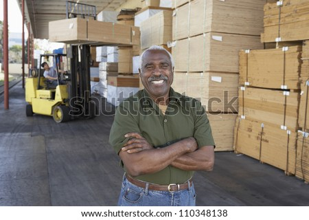 Portrait of happy man with arms crossed and man driving fork truck - stock photo