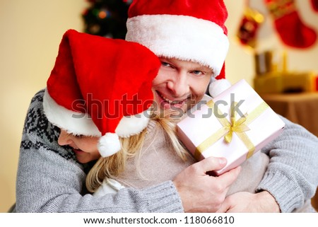 Portrait of happy man with giftbox embracing his joyful wife on xmas day - stock photo