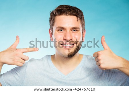 Portrait of happy man with half shaved face beard hair. Smiling handsome guy on blue showing thumb up gesture. Skin care and hygiene. - stock photo