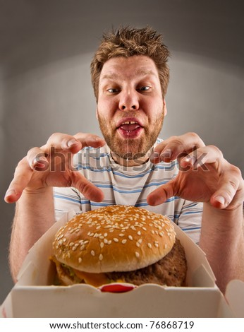 Portrait of happy man with leaking saliva preparing to eat burger - stock photo