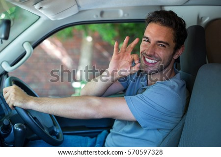 Portrait of happy man with ok sign while driving van
