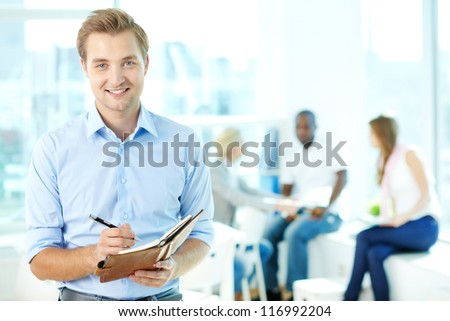 Portrait of happy man with pen and notepad looking at camera in working environment - stock photo