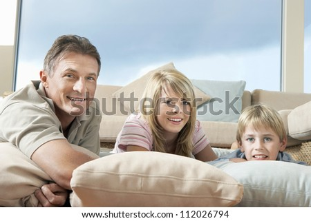 Portrait of happy man with son and daughter smiling at home