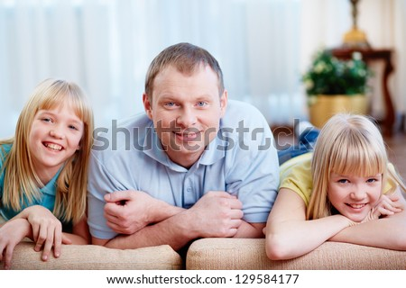 Portrait of happy man with twin daughters looking at camera