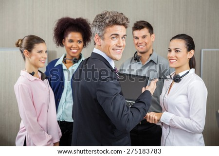 Portrait of happy manager in meeting with customer service representatives at call center