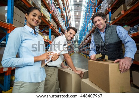 Portrait of happy managers are posing during work in a warehouse