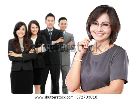 portrait of happy mature business women crossed arms with her employees at the background - stock photo