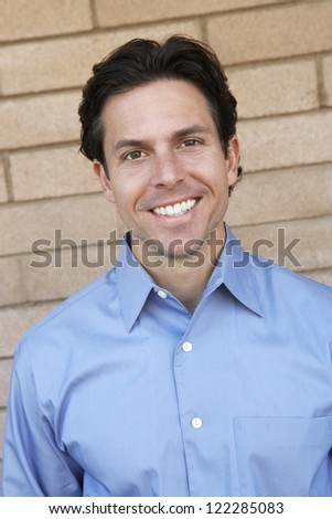Portrait of happy mature businessman against brick wall