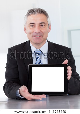 Portrait Of Happy Mature Businessman Holding Digital Tablet - stock photo