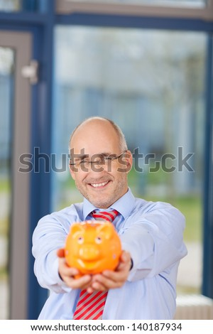 Portrait of happy mature businessman holding piggy bank in office - stock photo