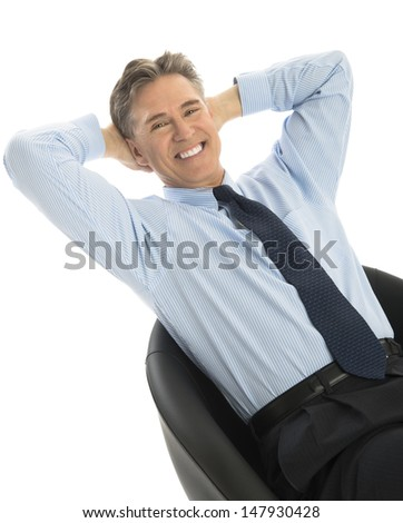 Portrait of happy mature businessman relaxing on office chair against white background - stock photo