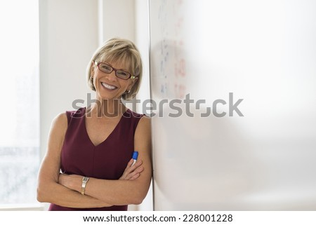 Portrait of happy mature businesswoman leaning on whiteboard in office - stock photo