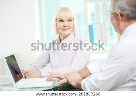 Portrait of happy mature businesswoman looking at her partner during discussion - stock photo