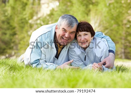 Portrait of happy mature couple in green grass - stock photo