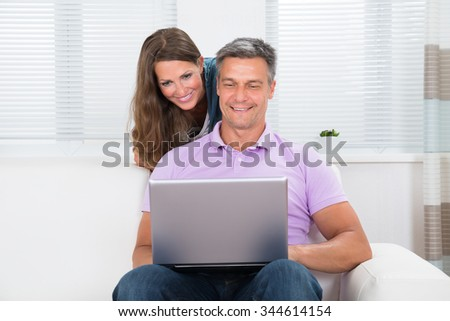 Portrait Of Happy Mature Couple Looking At Laptop