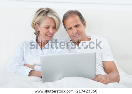 Portrait Of Happy Mature Couple On Bed Using Laptop - stock photo