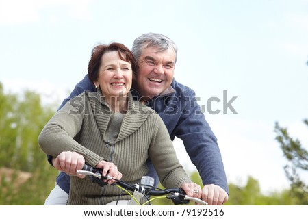 Portrait of happy mature couple on bicycle together - stock photo