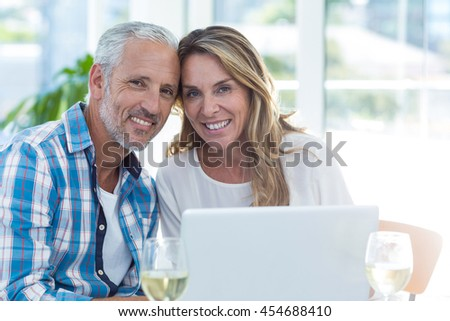Portrait of happy mature couple sitting by table in restaurant - stock photo