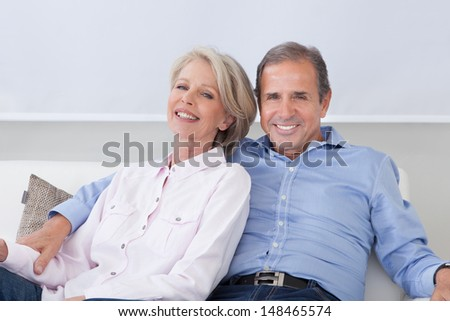 Portrait Of Happy Mature Couple Sitting Side By Side - stock photo