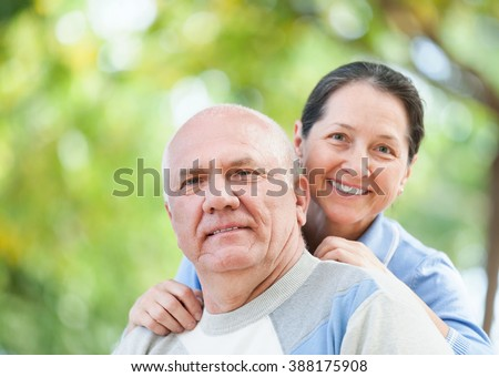 Portrait of happy mature couple together in autumn park - stock photo