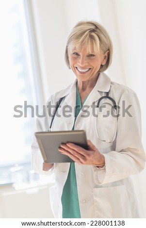 Portrait of happy mature female doctor using digital tablet in hospital - stock photo