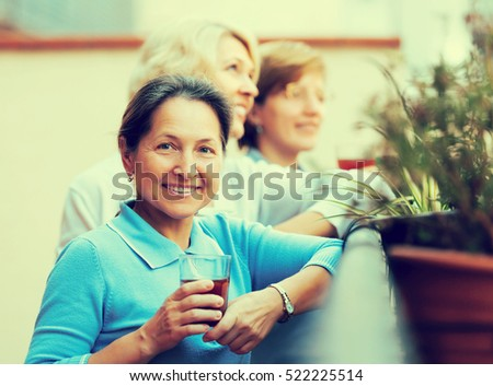 Portrait of happy mature female friends on summer terrace. Focus on brunette female