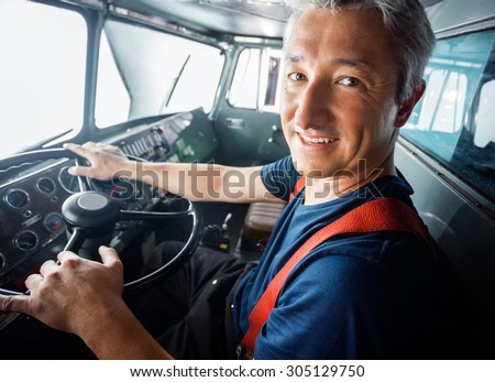 Portrait of happy mature firefighter driving firetruck - stock photo