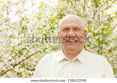 Portrait of  happy mature man near flowering trees