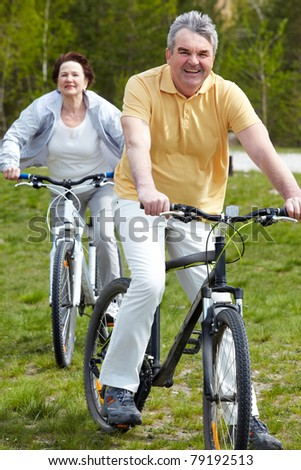 Portrait of happy mature man on bicycle with senior woman on background - stock photo