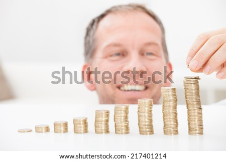 Portrait Of Happy Mature Man Sitting At Home Stacking Coins - stock photo