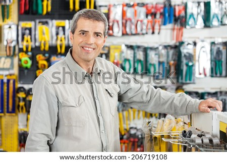 Portrait of happy mature man standing in hardware store