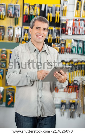 Portrait of happy mature man using digital tablet in hardware store