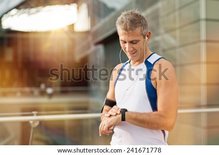 Portrait Of Happy Mature Man With Heart Rate Monitor On Wrist - stock photo