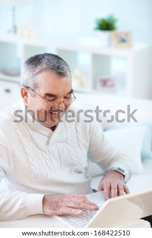 Portrait of happy mature man working with laptop - stock photo