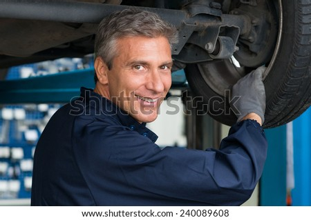 Portrait Of Happy Mature Mechanic At Repair Service Station Changing Tire - stock photo