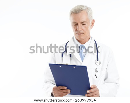 Portrait of happy mature medical doctor holding clipboard in hands while standing against white background.