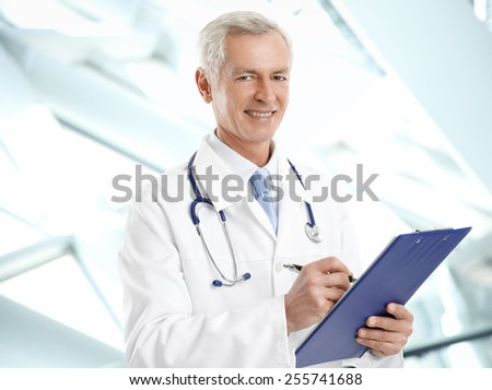 Portrait of happy mature medical doctor writing the result of medical test while standing at clinic. - stock photo