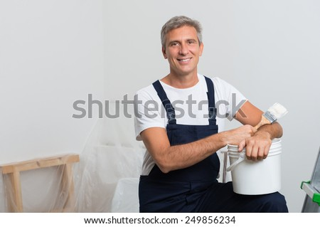 Portrait Of Happy Mature Painter With Stepladder And Paint Bucket - stock photo