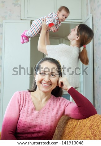 Portrait of happy mature woman against adult  daughter with little baby
