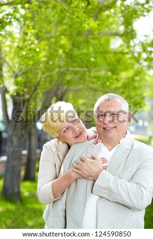 Portrait of happy mature woman hugging her husband and looking at him outside